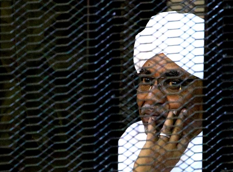 Sudan's former president Omar Hassan al-Bashir sits inside a cage at the courthouse where he is facing corruption charges, in Khartoum