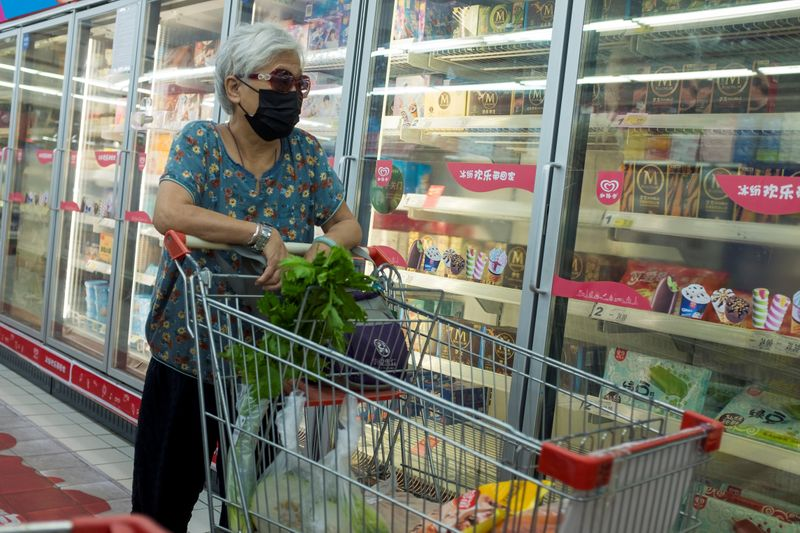 FILE PHOTO: A woman looks at frozen food products in a supermarket in Beijing