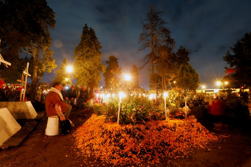 FILE PHOTO: People stand next to graves on the Day of the Dead to pay homage to their dead relatives