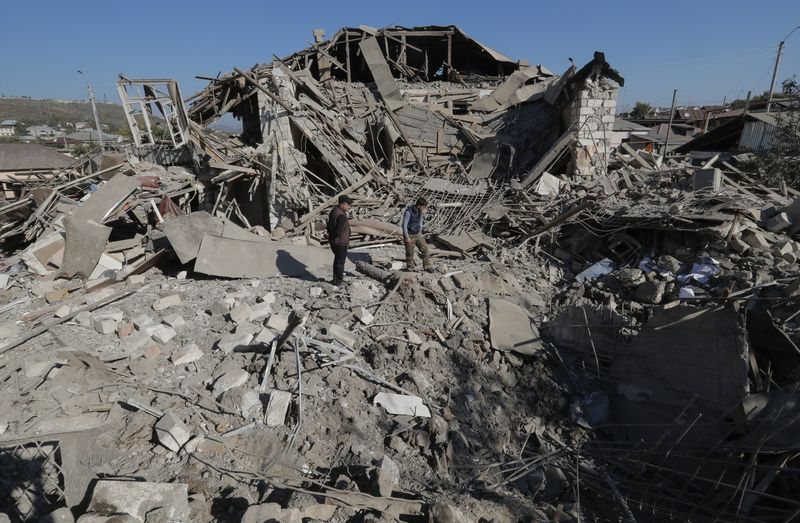 Men stand amidst the ruins of a house following recent shelling during a military conflict over the breakaway region of Nagorno-Karabakh, in Stepanakert