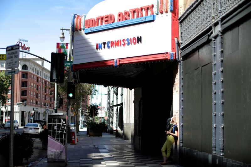 FILE PHOTO: A woman stands under a cinema entrance, as the global outbreak of the coronavirus disease (COVID-19) continues, in Los Angeles