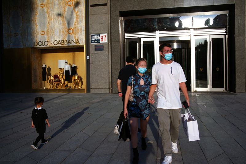 FILE PHOTO: People wearing face masks following the COVID-19 outbreak walk out of a shopping mall in Beijing