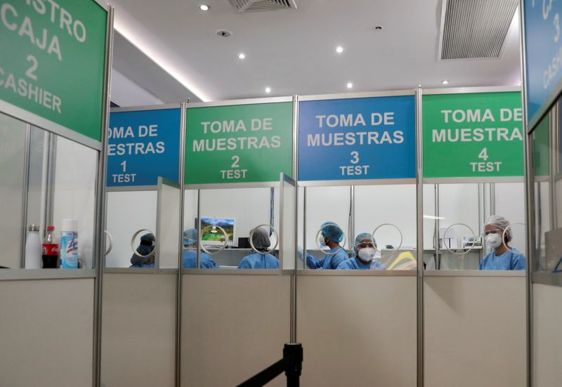 Healthcare workers sit in a booth offering coronavirus disease (COVID-19) tests for travelers at the Tocumen International Airport in Panama City