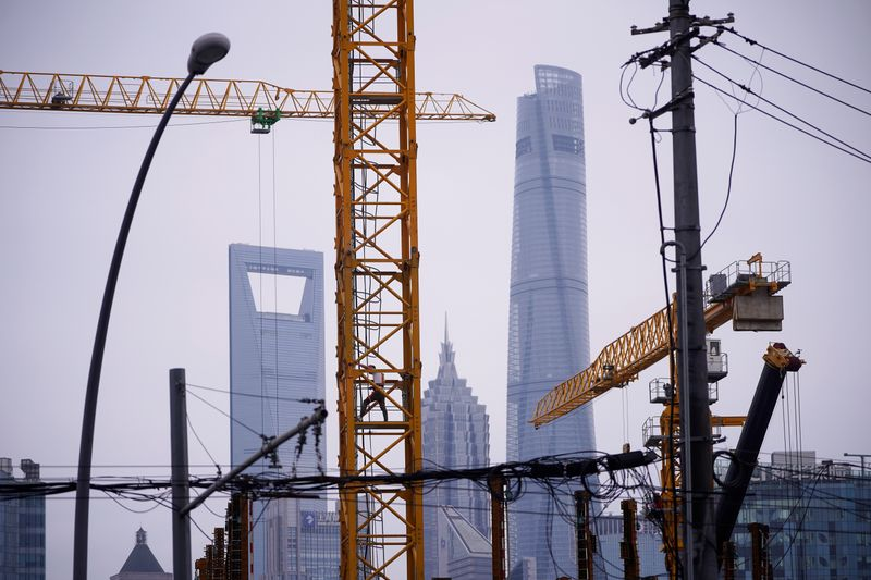 A worker is seen on a crane at a construction site in front of Lujiazui financial district, in Shanghai