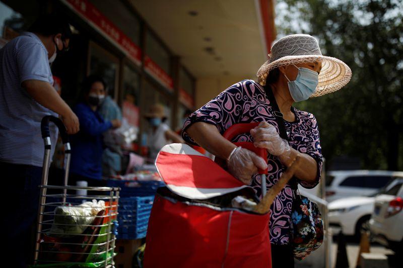 Woman holds a trolley outside a supermarket in Beijing
