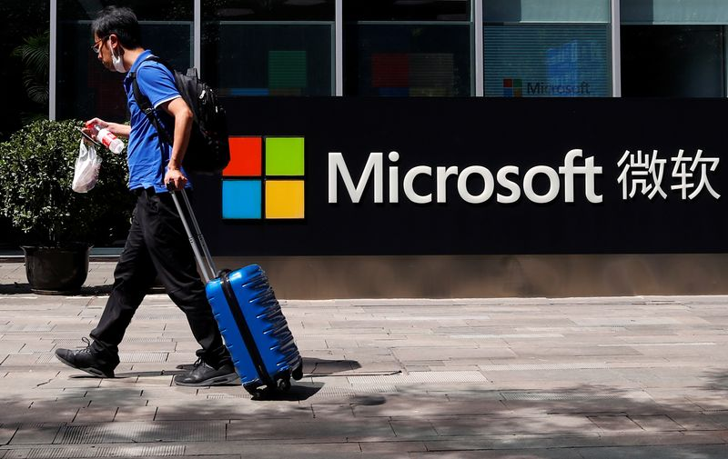 A person walks past a Microsoft logo at the Microsoft office in Beijing