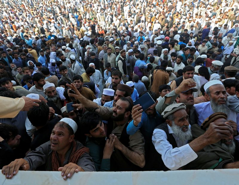 Afghan men wait to collect tokens needed to apply for the Pakistan visa, in Jalalabad, Afghanistan