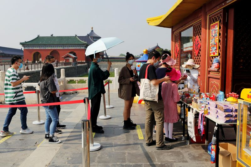 Visitors practise social distancing as they line up outside a souvenir shop at the Temple of Heaven in Beijing
