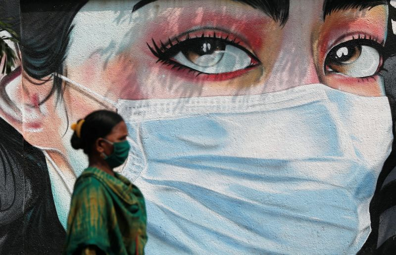 A woman walks past a graffiti of a girl wearing a protective mask amidst the spread of the coronavirus disease (COVID-19) in Mumbai