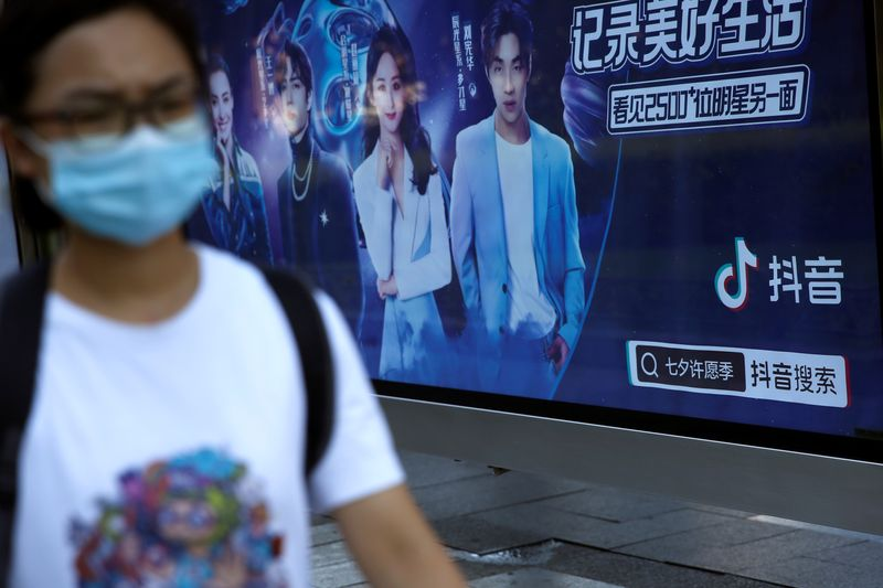 Pedestrian wearing a face mask following the coronavirus disease (COVID-19) outbreak walks past an advertisement of TikTok (Douyin) at a bus stop in Beijing