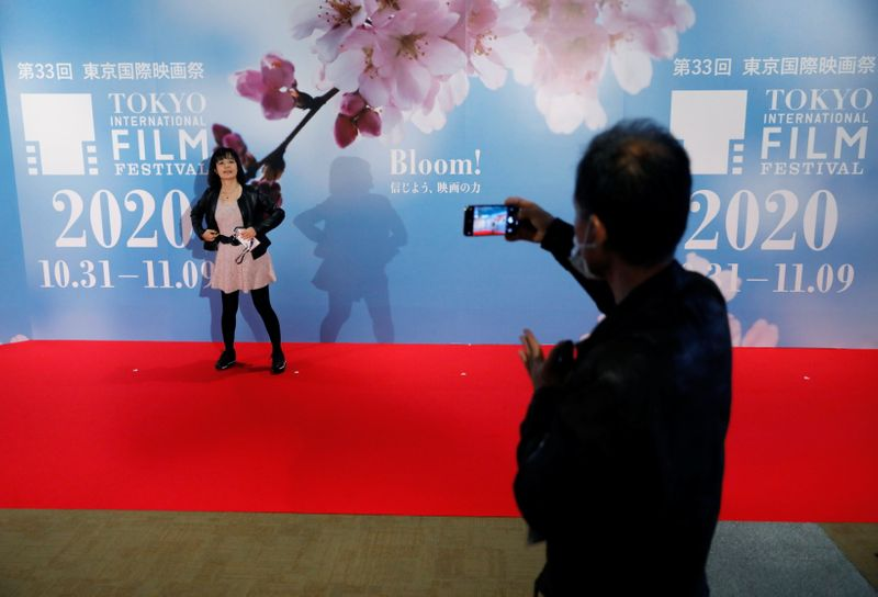 Visitors take photo on the red carpet at an entrance gate of the the 33rd Tokyo International Film Festival, amid the coronavirus disease (COVID-19) outbreak, in Tokyo
