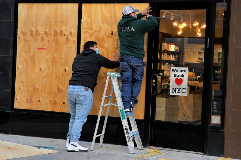 Workers board up a store ahead of election results in Manhattan, New York