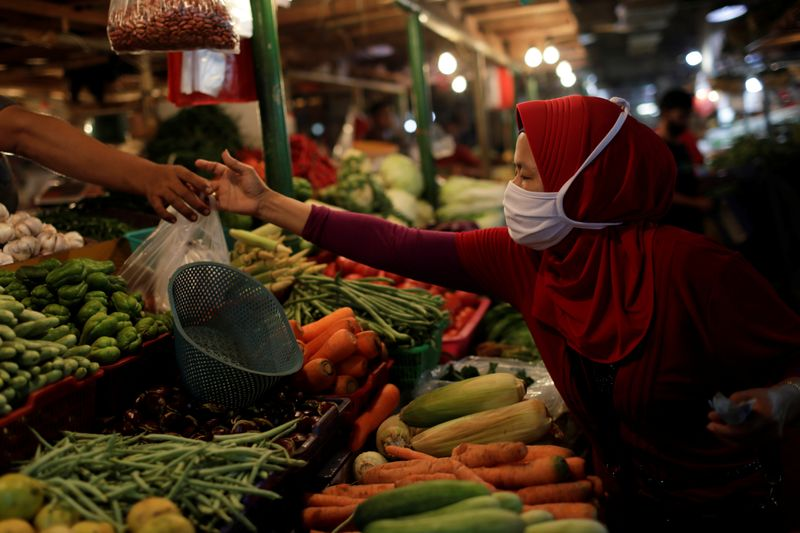 A woman wearing a protective mask shops for vegetables at a traditional market, as the coronavirus disease (COVID-19) outbreak continues, in Jakarta
