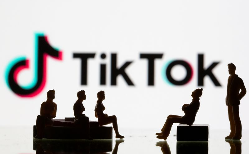 Small toy figures are seen in front of a Tiktok logo in this illustration taken
