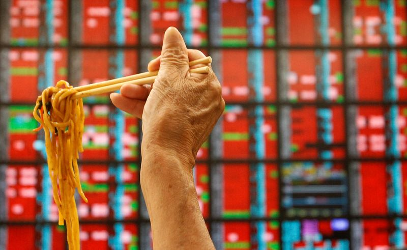 FILE PHOTO: A man eats his lunch of noodles while monitoring stock market prices inside a brokerage in Taipei