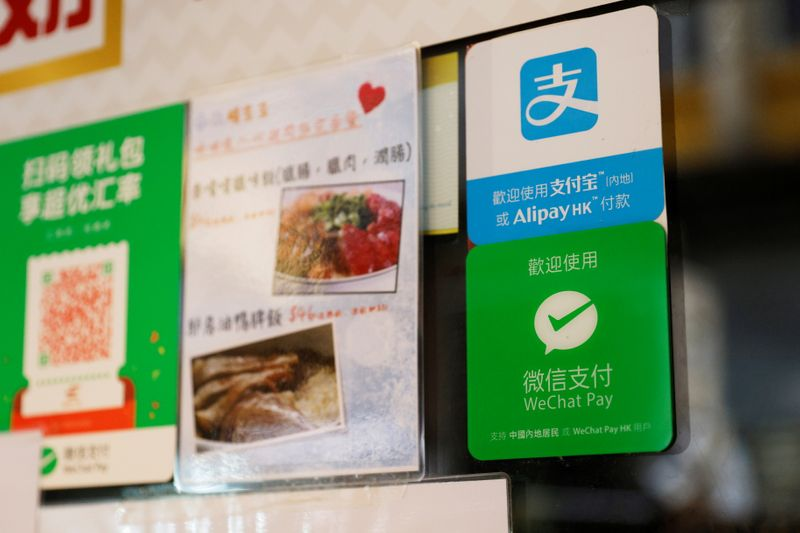 Logos for digital payment services Alipay by Ant Group, an affiliate of Alibaba Group Holding and WeChat Pay by Tencent Holdings are displayed outside a restaurant, in Hong Kong