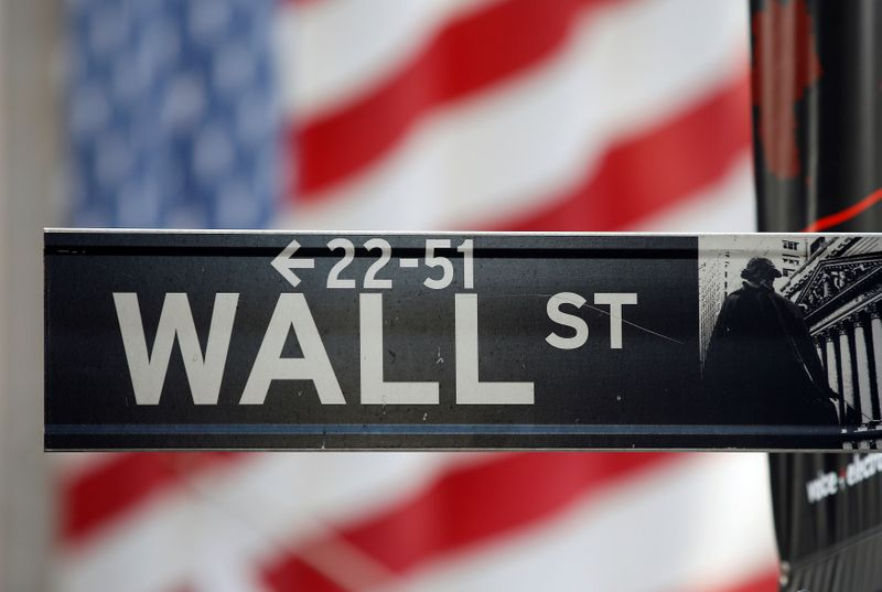 FILE PHOTO: A sign for Wall Street is seen with a giant American flag in the background across from the New York Stock Exchange