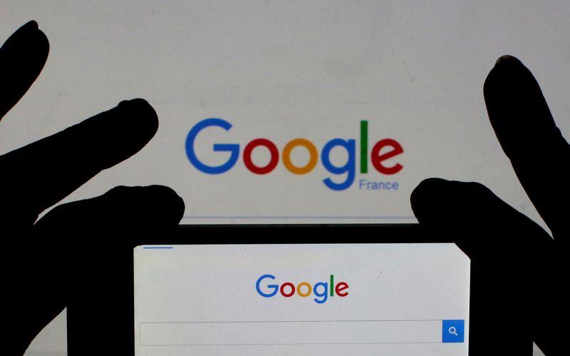FILE PHOTO: File photo of a woman holding her smart phone which displays the Google home page, in this picture illustration