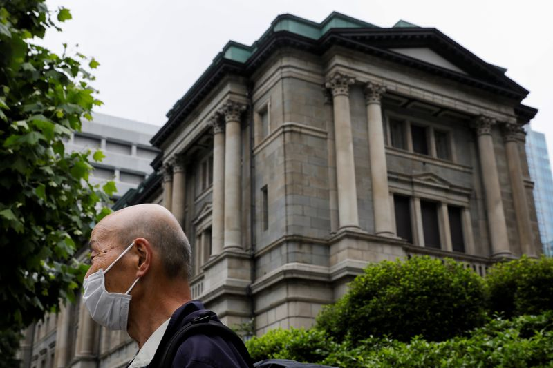A man wearing a protective mask stands in front of the headquarters of Bank of Japan amid the coronavirus disease (COVID-19) outbreak in Tokyo