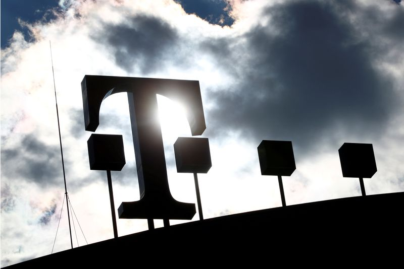 FILE PHOTO: Logo of Deutsche Telekom AG is silhouetted atop of the headquarters of the German telecommunications giant in Bonn