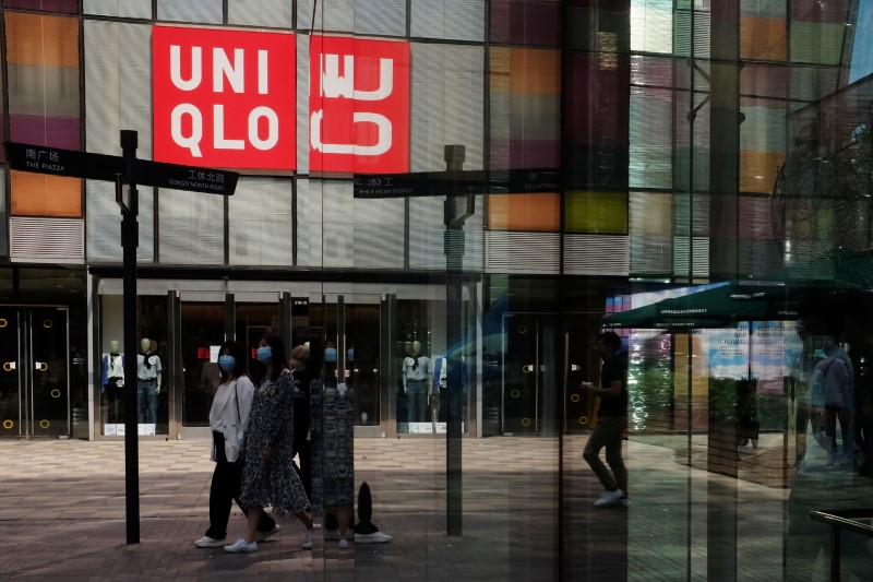 Women walk past a store of the Fast Retailing's fashion chain Uniqlo, in Beijing