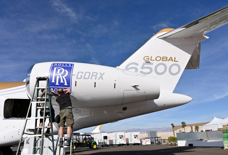 Workers apply a Rolls Royce decal to the engine of a Bombardier Global 6500 business jet at the Bombardier booth at the National Business Aviation Association (NBAA) exhibition in Las Vegas