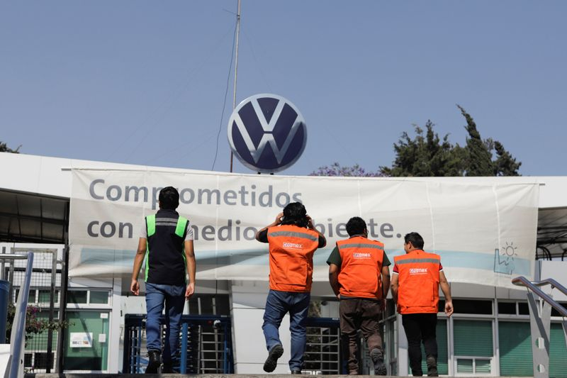 Workers walk outside the Volkswagen (VW) plant as the company will temporarily close its factories in Mexico amid growing worries over the spread of the coronavirus disease (COVID-19), in Puebla