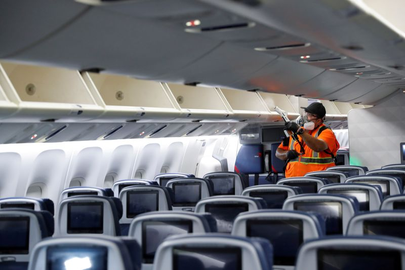 A Delta Air Lines pre-flight cleaning crew member uses an electrostatic disinfection device to clean an aircraft at JFK International Airport in New York
