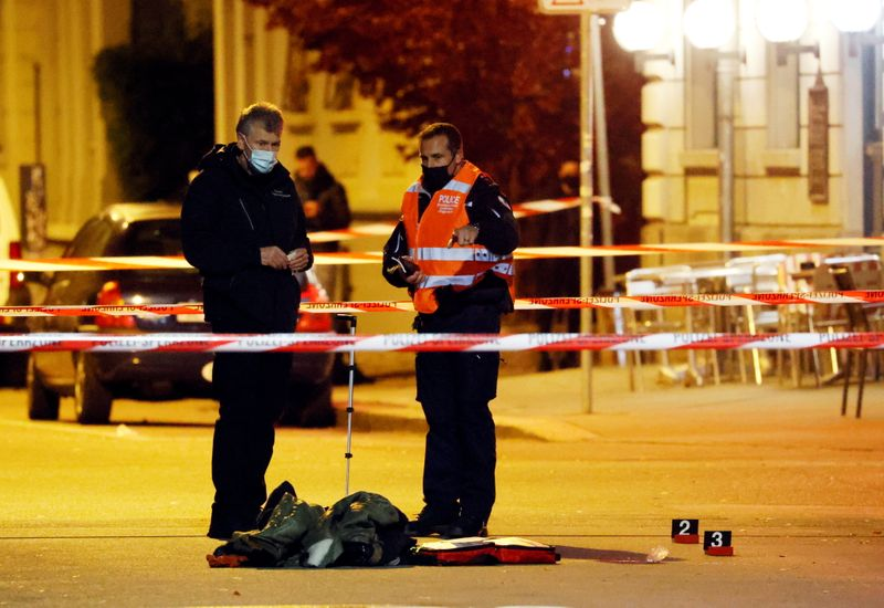 Police officers survey the site of a shooting in Biel