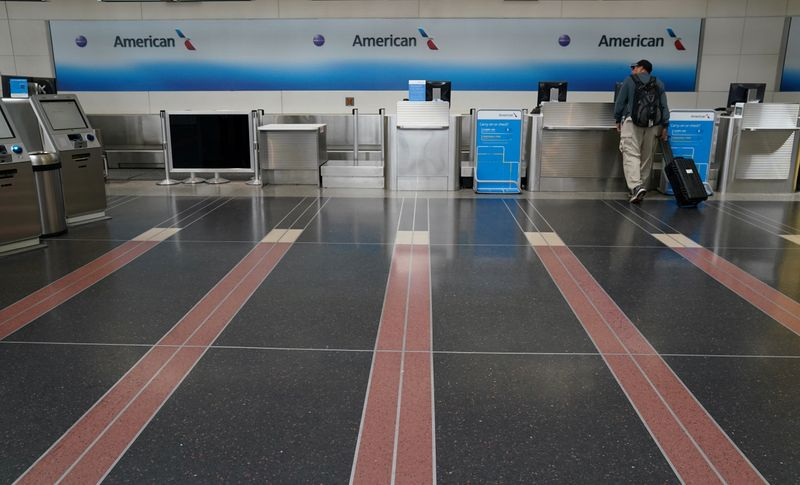 FILE PHOTO: Customer seeks assistance at American Airlines counter at Reagan National airport in Washington
