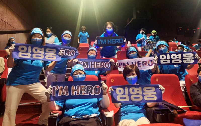 Fans of South Korean singer Lim Young-woong pose for photographs with banners bearing his name, before watching a movie featuring