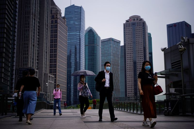 People wearing protective face masks walk past office buildings in Lujiazui financial district in Pudong, in Shanghai