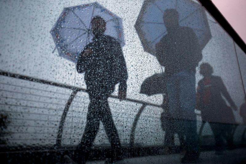 FILE PHOTO: Pedestrians walk across the Millennium Footbridge during rainy weather in London