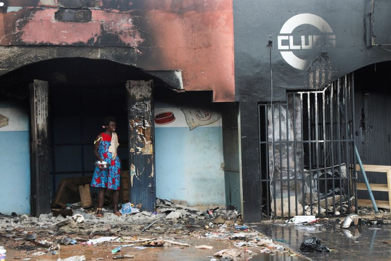 A woman stands near the rubble of a burnt store after post electoral inter-community clashes, in M'Batto