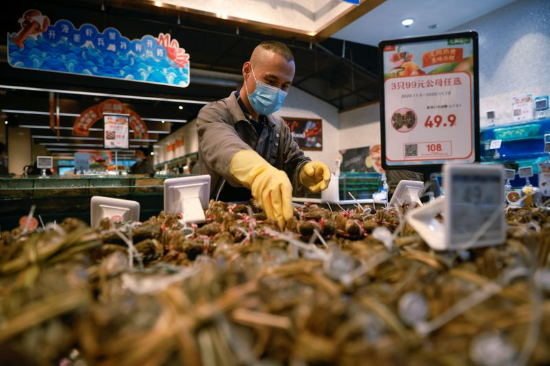 A staff member lays out seafood at a supermarket in Beijing