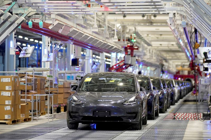FILE PHOTO: FILE PHOTO: FILE PHOTO: Tesla China-made Model 3 vehicles are seen during a delivery event at its factory in Shanghai