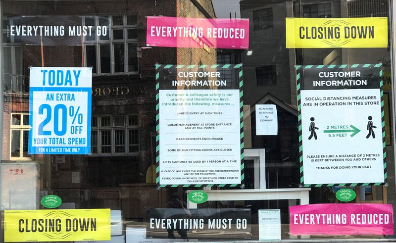 FILE PHOTO: Closing down, reductions and social distancing posters are seen in a closed retail shop window in London