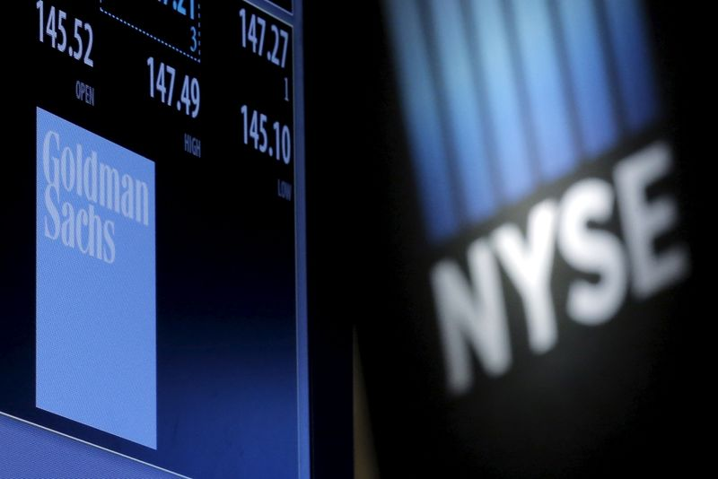 A screen displays the ticker symbol and information for Goldman Sachs on the floor of the New York Stock Exchange
