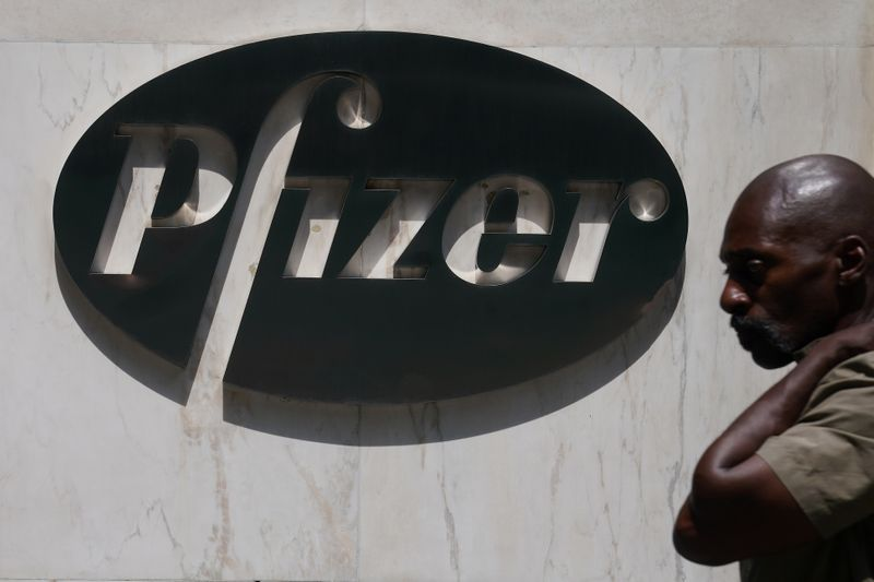 A man walks past a sign outside Pfizer Headquarters in the Manhattan borough of New York City