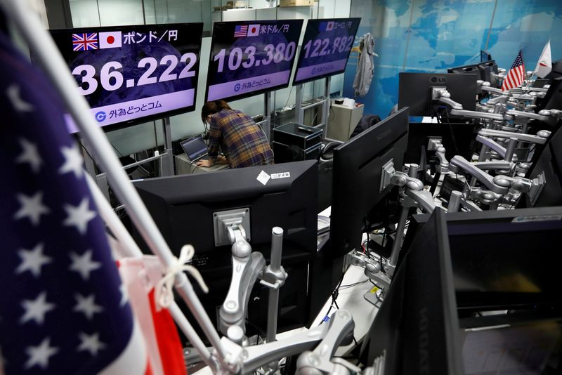 FILE PHOTO: An employee of the foreign exchange trading company works in front of monitors showing the Japanese yen exchange rate against foreign currencies at a dealing room in Tokyo