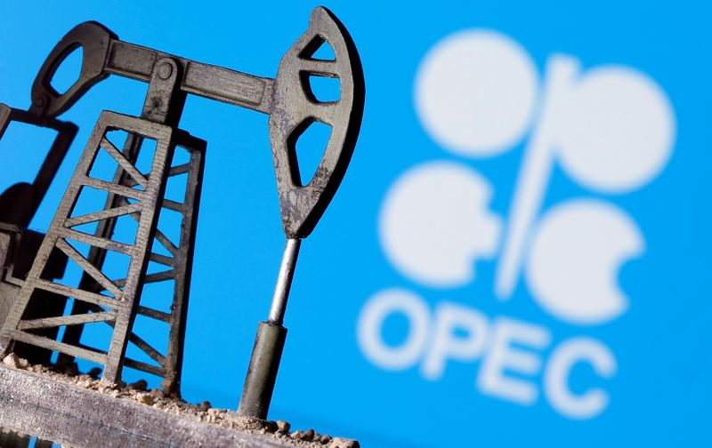 A 3D printed oil pump jack is seen in front of displayed Opec logo in this illustration picture