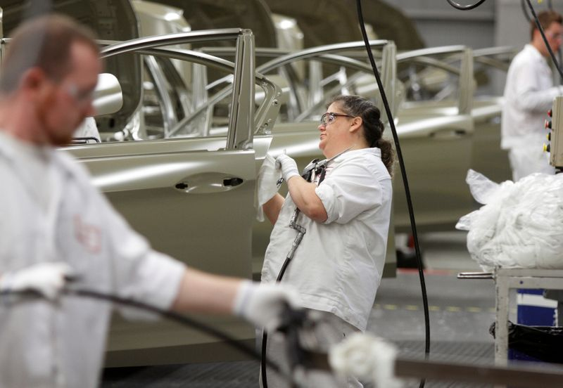 An employee works on the sealer line in the paint department during a tour of an automobile plant in Marysville