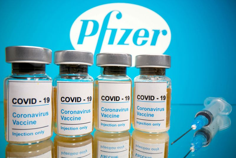 FILE PHOTO: FILE PHOTO: FILE PHOTO: FILE PHOTO: FILE PHOTO: Vials and medical syringe are seen in front of Pfizer logo in this illustration