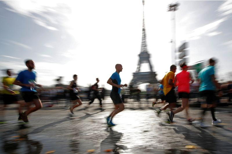 Runners make their way past the Eiffel Tower as they participate in the 42nd Paris Marathon