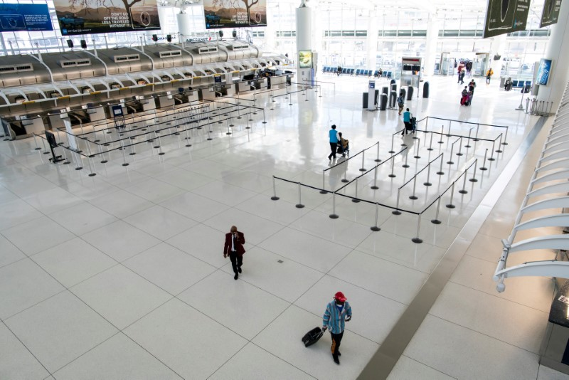 FILE PHOTO: People walk around the terminal at the John F. Kennedy International Airport in New York