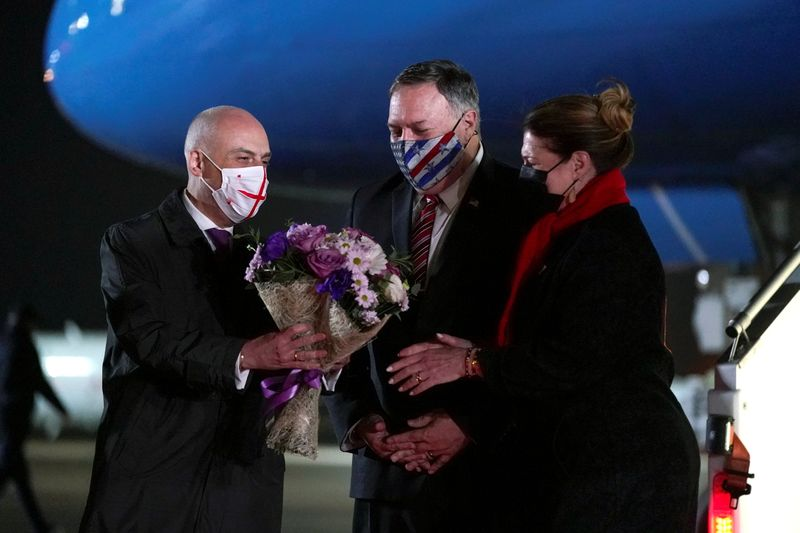 Georgian Foreign Minister David Zalkaliani gives flowers to Susan Pompeo as she and U.S. Secretary of State Mike Pompeo, arrive at Tbilisi International Airport