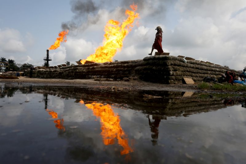 FILE PHOTO: A reflection of two gas flaring furnaces and a woman walking on sand barriers is seen in the pool of oil-smeared water at a flow station in Ughelli, Delta State