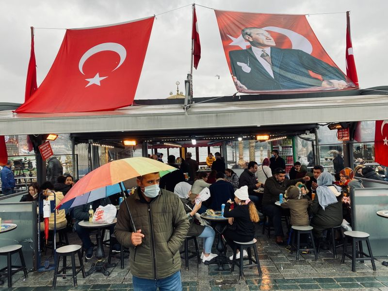 Man wearing a protective mask stands in front of a fish and bread restaurant in Istanbul