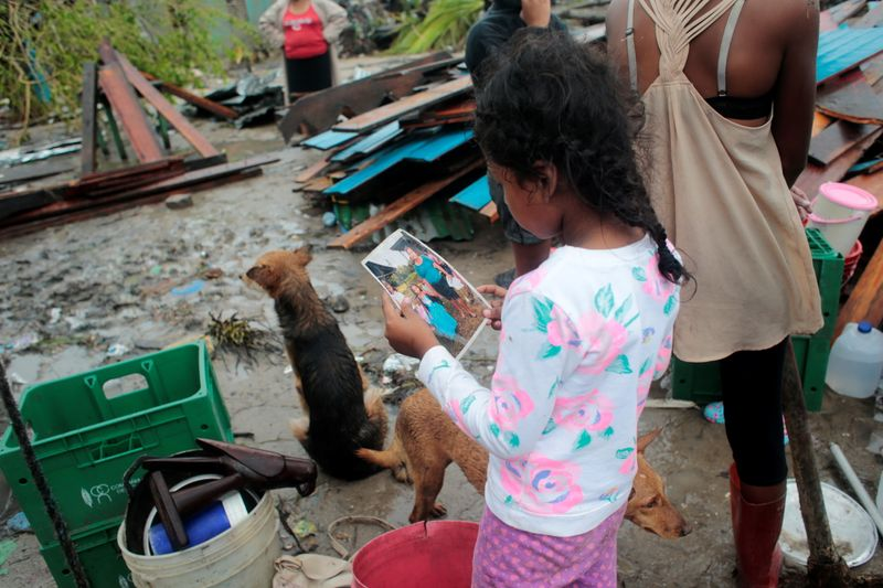 A girl looks at a family photo recovered from the debris of her house destroyed after the passing of Hurricane Iota, in Puerto Cabezas