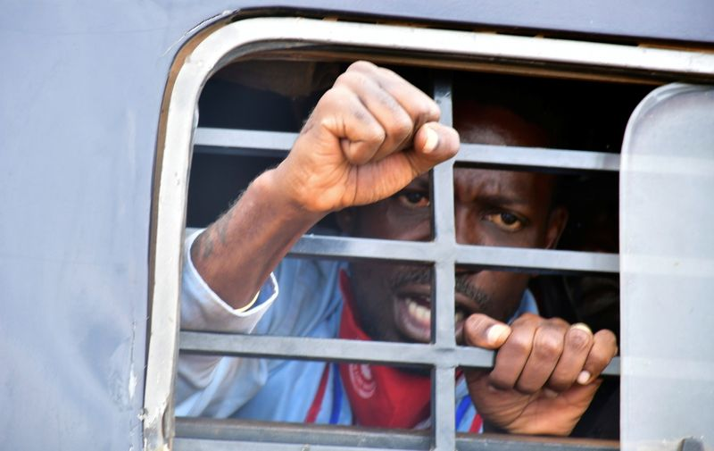 Ugandan presidential candidate Robert Kyagulanyi reacts from inside a police van, in Luuka district